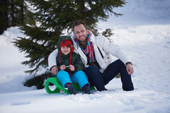 Portrait of father and son on snow. Sitting on sled at beautiful sunny winter day Royalty Free Stock Photos