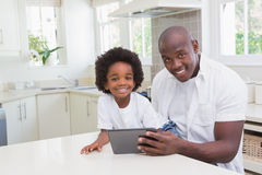 Portrait of a father and son using digital tablet Stock Photos