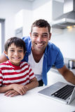 Portrait of father and son using laptop in kitchen. At home stock image