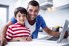 Portrait of father and son using laptop in kitchen. At home royalty free stock photography
