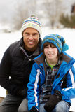 Portrait Of Father And Son Wearing Winter Clothes. In Snowy Landscape Stock Photography