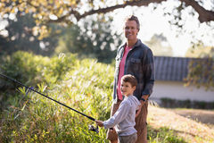 Portrait of father standing by boy holding fishing rod. Portrait of mature father standing by boy holding fishing rod in forest stock photography