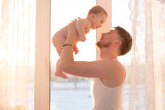 Portrait of father standing near the window with baby Stock Photos