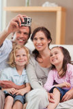 Portrait of a father taking a picture of his family. In a living room Royalty Free Stock Photography