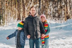 Portrait of father and two kids enjoying winter forest. On a nice sunny day stock images