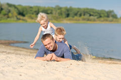 Portrait of a father and two sons. On the beach Stock Photos