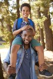 Portrait Of Father Walking In Woods Carrying Son On Shoulders stock photography