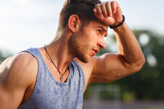 Portrait of fatigued fitness guy on hot sunny day. Portrait of fatigued fitness guy after exercises on hot sunny day stock images