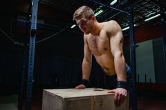 Portrait of fatigued fitness guy. Near the wooden cube. Cross fit style. stock images