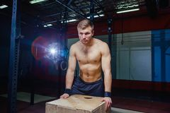 Portrait of fatigued fitness guy. Near the wooden cube. Crossfit style. Royalty Free Stock Photo