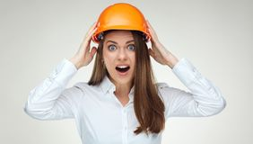 Portrait of fear emotion business woman touching head with build. Er helmet. Isolated white back Royalty Free Stock Photos