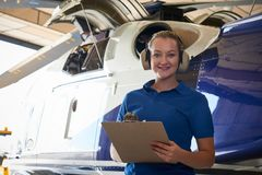 Portrait Of Female Aero Engineer With Clipboard Carrying Out Che. Ck On Helicopter royalty free stock image