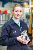 Portrait Of Female Apprentice Holding Component. Female Apprentice In Factory Holding Component stock photo
