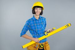 Female architect holding measuring equipment against grey background Royalty Free Stock Images