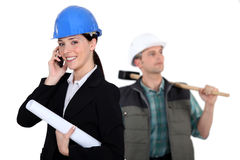 Portrait of female architect making a call. And carpenter in background Royalty Free Stock Photos