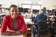 Portrait Of Female Architect With Meeting In Background. Portrait Of Female Architect Smiling At Camera With Meeting In Background In Office Stock Image