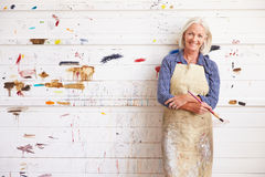 Portrait Of Female Artist Against Paint Covered Wall Stock Photography