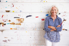 Portrait Of Female Artist Against Paint Covered Wall Royalty Free Stock Photos