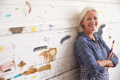 Portrait Of Female Artist Against Paint Covered Wall Stock Image
