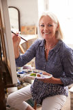 Portrait Of Female Artist Working On Painting In Studio Royalty Free Stock Photography