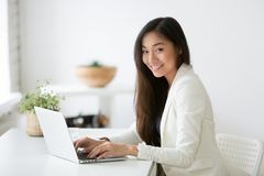 Portrait of female Asian professional posing smiling at camera. Portrait of beautiful Asian female office worker looking at camera smiling while working at stock photo