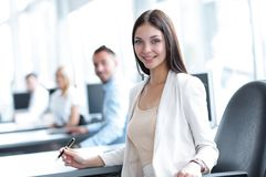 Portrait of a female assistant sitting at a Desk Stock Photography