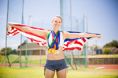 Portrait of female athlete holding up american flag with gold medal. In stadium Stock Photography