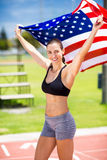 Portrait of female athlete holding up american flag on running track Royalty Free Stock Photo