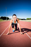 Portrait of female athlete in ready to run position stock photo