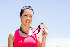 Portrait of female athlete showing her gold medal. Portrait of happy female athlete showing her gold medal Royalty Free Stock Photography