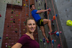 Portrait of female athlete standing against trainer climbing wall Royalty Free Stock Images