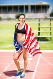 Portrait of female athlete wrapped in american flag. On running track Stock Photo