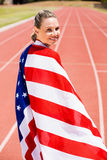 Portrait of female athlete wrapped in american flag. On running track Royalty Free Stock Photos