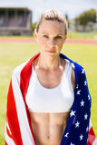 Portrait of female athlete wrapped in american flag. In stadium Royalty Free Stock Photo