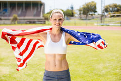Portrait of female athlete wrapped in american flag. In stadium Royalty Free Stock Image