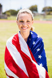 Portrait of female athlete wrapped in american flag. In stadium Royalty Free Stock Images