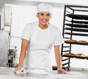 Portrait Of Female Baker Cleaning Flour From Table Stock Photos