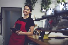 Portrait of female barista smiling to the camera holding cup of coffee stock photo