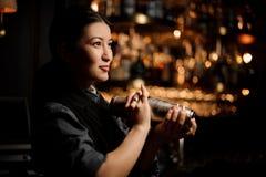 Portrait of female bartender holding shaker at bar counter. Portrait of cute female bartender holding stainless steel shaker at the bar counter royalty free stock photo