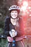 Portrait of female biker with mountain bike in countryside Stock Photography