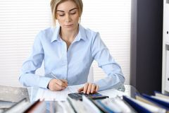 Portrait of female bookkeeper or financial inspector  making report, calculating or checking balance. Copy space area.  Stock Image