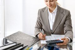 Portrait of female bookkeeper or financial inspector  making report, calculating or checking balance. Copy space area.  Stock Images