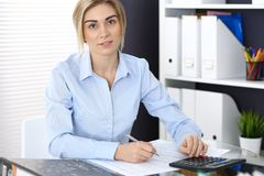 Portrait of female bookkeeper or financial inspector  making report, calculating or checking balance. Copy space area.  Stock Photos