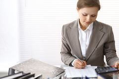 Portrait of female bookkeeper or financial inspector  making report, calculating or checking balance. Copy space area.  Royalty Free Stock Image