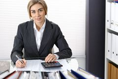 Portrait of female bookkeeper or financial inspector  making report, calculating or checking balance. Copy space area.  Stock Photography