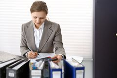 Portrait of female bookkeeper or financial inspector  making report, calculating or checking balance. Copy space area.  Stock Photo