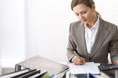 Portrait of female bookkeeper or financial inspector  making report, calculating or checking balance. Copy space area.  Royalty Free Stock Photo