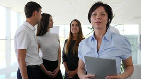 Portrait of female boss who speaks with collaborators and smiling in office stock video footage