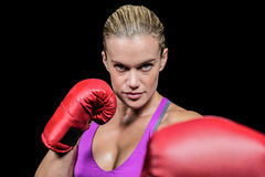 Portrait of female boxer with fighting stance. Against black background stock photography