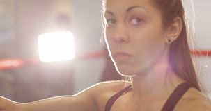 Portrait of female boxer with her arm on the punching bag. Portrait of a sporty and serious female athletic boxer resting with her arm on the punching bag. Slow stock video footage